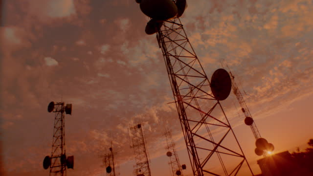 ORANGE CANTED low angle time lapse clouds behind antenna towers at sunset