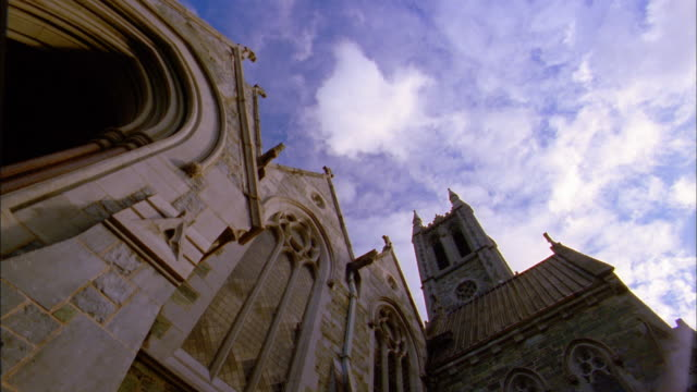 Low angle time lapse clouds passing over stone church exterior / Ireland
