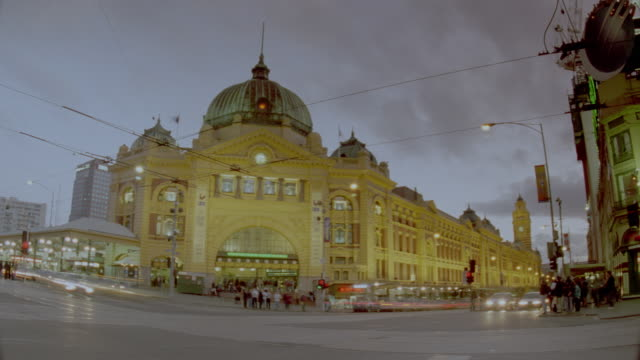 low angle time lapse traffic in front of Flinders Street Station at dusk / Melbourne, Victoria, Australia