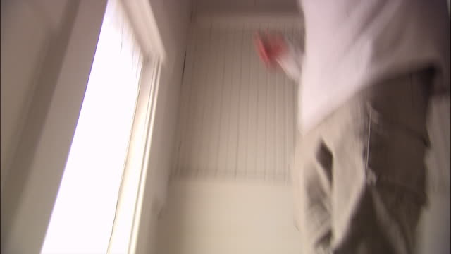 Low angle tracking shot close up man walking down stairs cluttered with toys
