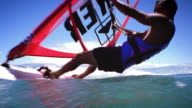 Low angle tracking shot man windsurfing and leaning with back near water while passing over camera, splashing lens /Hawaii