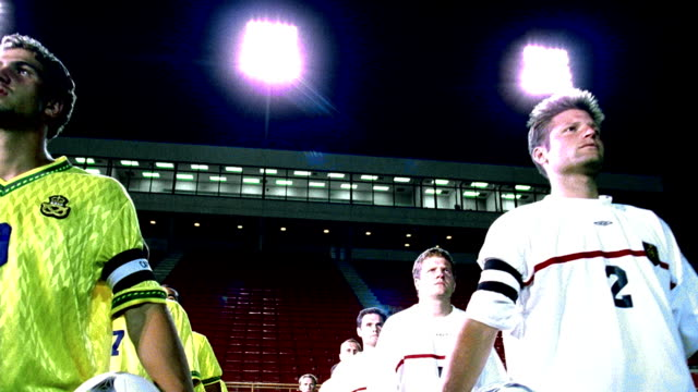 low angle tracking shot players for 2 soccer teams walking onto field in empty stadium at night