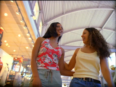 low angle tracking shot two Black women walking + waving + pointing in shopping mall
