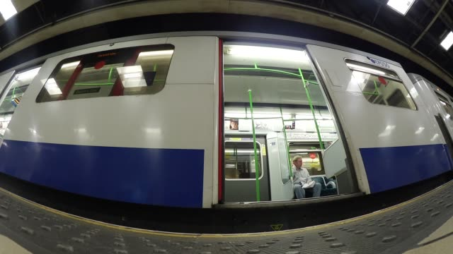 Low angle view filmed with a fish eye lens showing a London Underground station platform as a tube train arrives commuters step from carriage and...