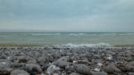 A low angle view looking across a calm overcast English Channel with gently lapping waves splashing over a pebble shoreline