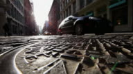 WS low angle View of cars running on shining stone pavement street at Soho / New York, United States