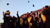Low angle view of college students celebrating graduation day in the college