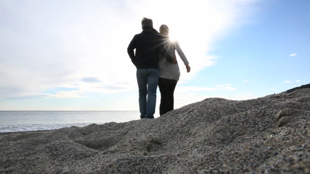 Low angle view of couple walking along sandy beach
