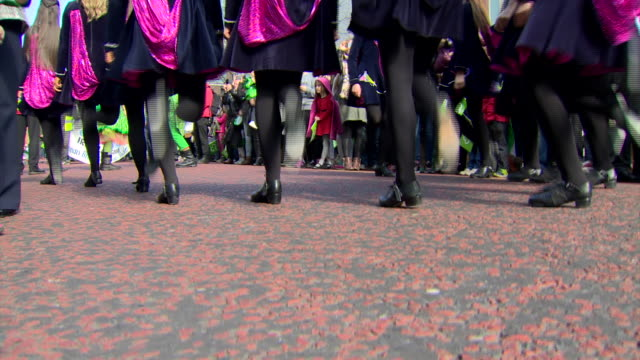 Low angle view of Irish dancers legs followed by a pan to reveal a float featuring a leprechaun at the St Patricks day parade in Belfast