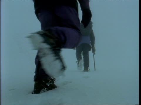 MS low angle view of people's spiked boots trekking up snowy mountainside, Rwenzori Mountains, Uganda