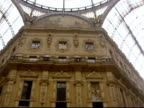 Low angle view of vaulted glass ceiling of Galleria Vittorio Emanuele II / pan to pedestrians walking past Prada store in arcade / Milan, Italy