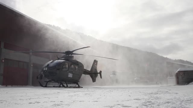 Low angle view Swiss Air Force helicopters parked at base one helicopter coming into land on snowy ground Army helicopters and pilots Swiss Air Force...