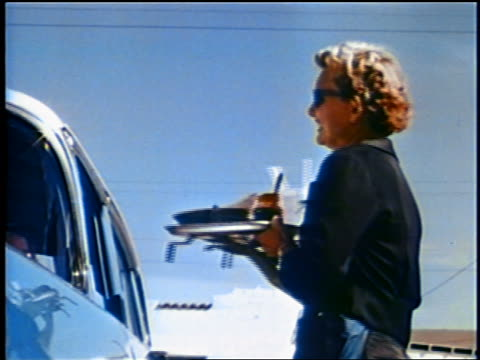 1958 low angle waitress removing food tray from car smiling + talking to person in car / newsreel