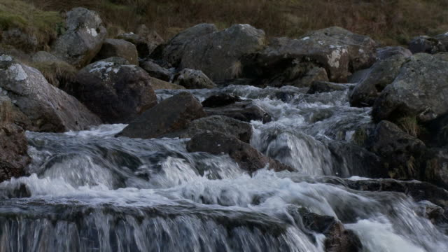 Low angle water flowing over rocks and boulders in mountain stream, Brecon Beacons, Wales