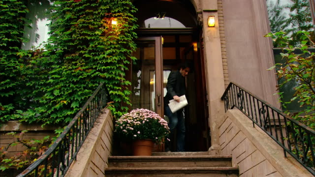 Low angle wide shot brownstone building covered with ivy/ tilt down stoop of building with man walking out door and down steps/ Brooklyn, New York