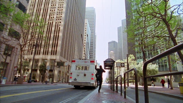 Low angle wide shot commuter on cell phone running to catch bus / San Francisco