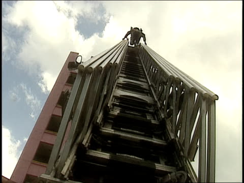 Low angle wide shot firefighter climbing ladder