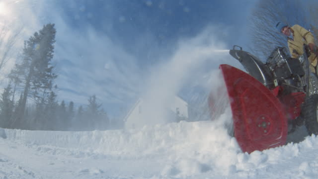 Low angle wide shot fisheye view of man blowing snow off sidewalk in front of house / Vermont
