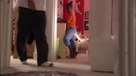 Low angle wide shot girl standing in bedroom / dad walking by and mom chasing younger brother with his pants in hall