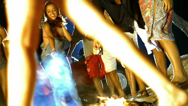 Low angle wide shot group of young people dancing around campfire / roasting hot dogs over flames