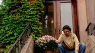 Low angle wide shot ivy on apartment building/ tilt down man sitting on steps talking on mobile phone/ Brooklyn, New York