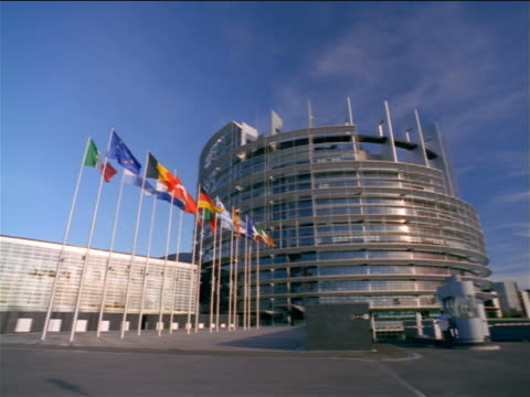 low angle wide shot PAN Louise Weiss EU Parliament building with flags in foreground / Strasbourg, France