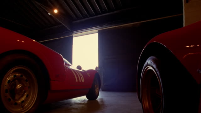 Low angle wide shot man opening garage doors / illuminiating vintage red sportscars