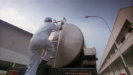 Low angle wide shot milk factory worker carrying pitcher up ladder on back of milk tanker to top of tank