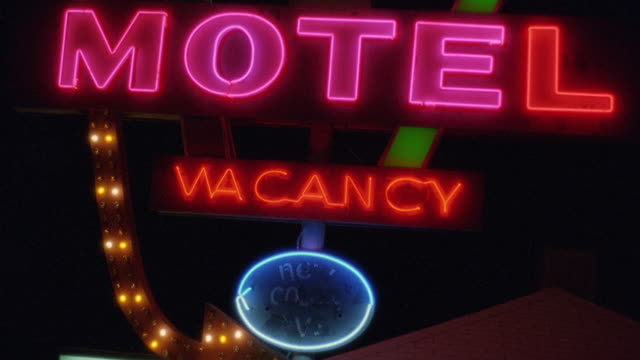 Low angle wide shot neon motel sign with 'vacancy' lit up / Arizona