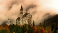 Low angle wide shot of Neuschwanstein Castle in Autumn with time lapse fog moving behind it / Bavaria, Germany
