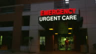 Low angle wide shot person exiting emergency room of hospital at dusk / Tucson, Arizona