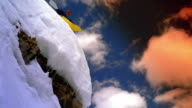 Low angle wide shot person snow kayaking over snow and ice covered rock on mountain face / Aspen, Colorado