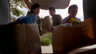 Low angle wide shot point of view father opening hatchback /family taking grocery bags out of back of car and walking to house