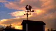 low angle wide shot SILHOUETTE weather vane on top of barn with time lapse clouds moving in background at sunset / New England