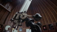 Low angle wide shot tilt down tilt up roof retracting as boy enters observatory / boy looking through telescope