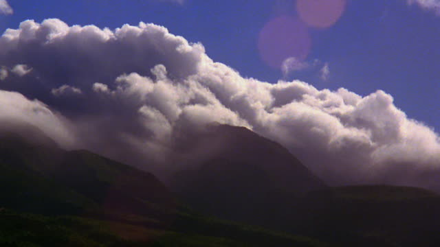 Low angle wide shot time lapse clouds rolling down mountainside / Hawaii
