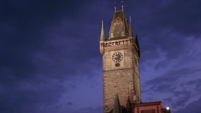 Low angle wide shot time lapse clouds rolling over Prague Old Town Hall clock tower at dusk / Prague, Czech Republic