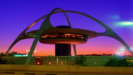 Low angle wide shot time lapse Los Angeles Airport Theme Building (Encounter) with traffic in foreground at dusk / California