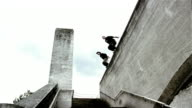 Low angle wide shot two freerunners jumping off roof and grabbing ledge / pulling themselves up