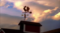 low angle wide shot weather vane on top of barn with clouds moving in background at sunset / New England