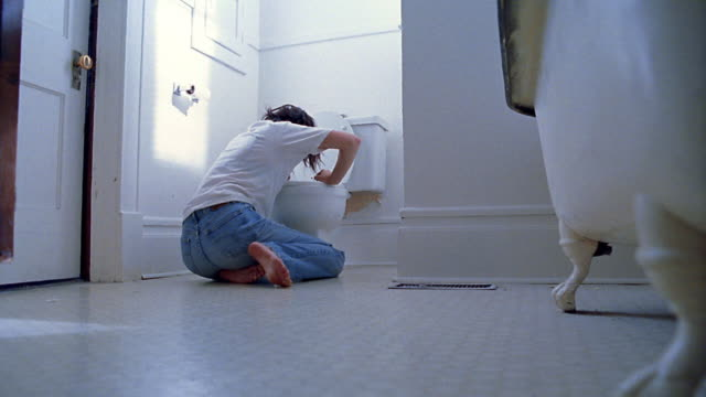 Low angle wide shot woman kneeling over toilet and vomiting in bathroom, then leaning against wall