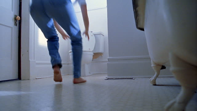 Low angle wide shot woman running in to bathroom, kneeling and vomiting in toilet