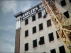 1961 low angle wide shot wrecking ball swinging from crane and smashing into building