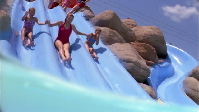 Low angle woman and two girls holding hands + sliding down water slide into pool