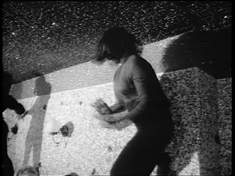 B/W 1965 low angle woman in black tights dancing on table in nightclub / newsreel