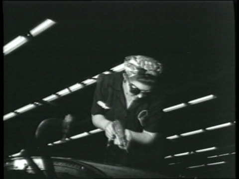 B/W 1943 low angle woman in goggles using power tool in bomber factory