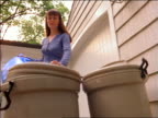 low angle woman putting full blue garbage bag into outdoor garbage can