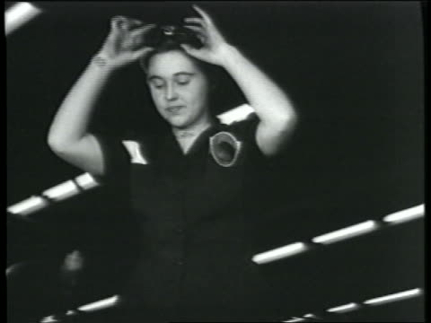 B/W 1943 low angle woman takes off goggles picks up power tool in bomber factory