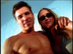 Low angle zoom in zoom out young couple posing against white background / man is shirtless / California