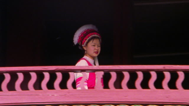 low angle PAN zoom out Bai woman in traditional dress walking on balcony / Dali, Yunnan Province, China
